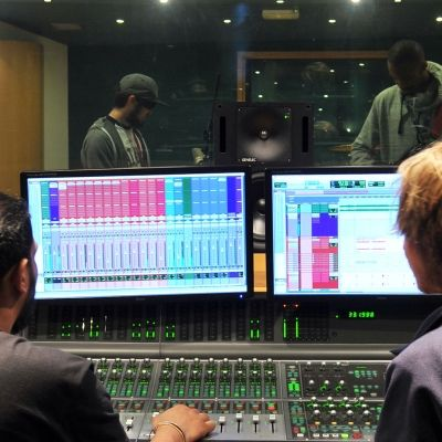 two men looking at two screens in a music studio