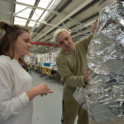 Two students look at a tin foil structure in the red shed