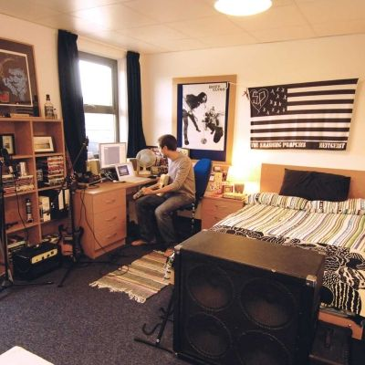 BNU student in Hughenden accommodation studio bedroom sitting at desk with musical equipment around