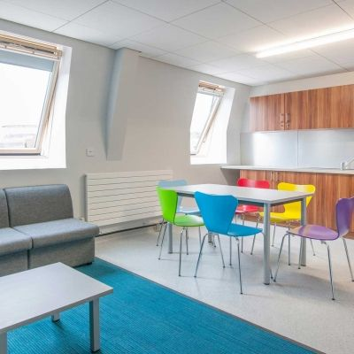 a sofa, table and chairs and kitchen fittings and equipment inside Windsor House accommodation