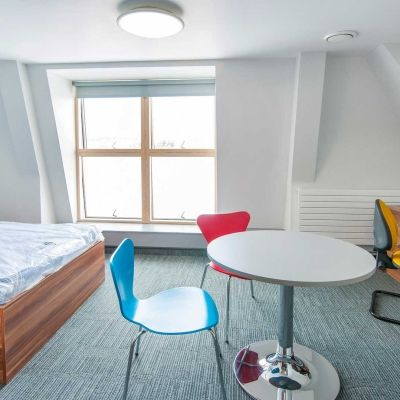 A bed, table, desk and chairs inside a Windsor House standard room accommodation