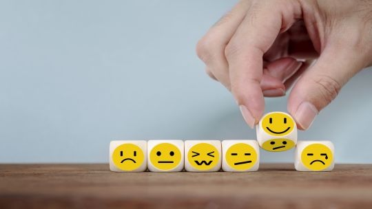 six mini cubes with different emoji face expressions on, all lined up together