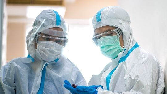 Two nurses in full protective equipment, including masks, gloves and visors
