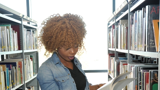 A lady reading a book standing up in the library