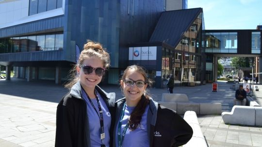 Two female Student Ambassadors outside the gateway building