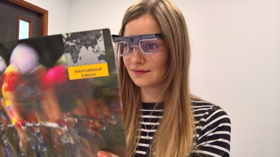 A woman reading whilst wearing eye tracking glasses