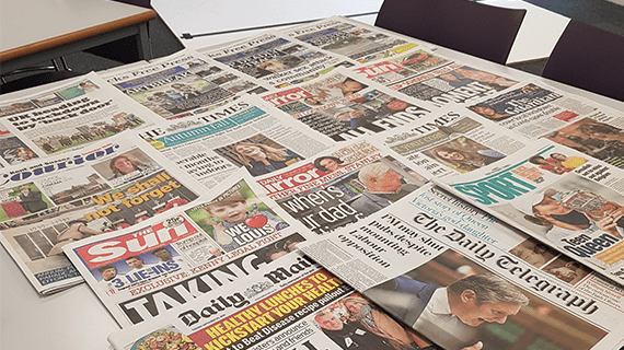Newspapers all laid out on a table overlapping one another