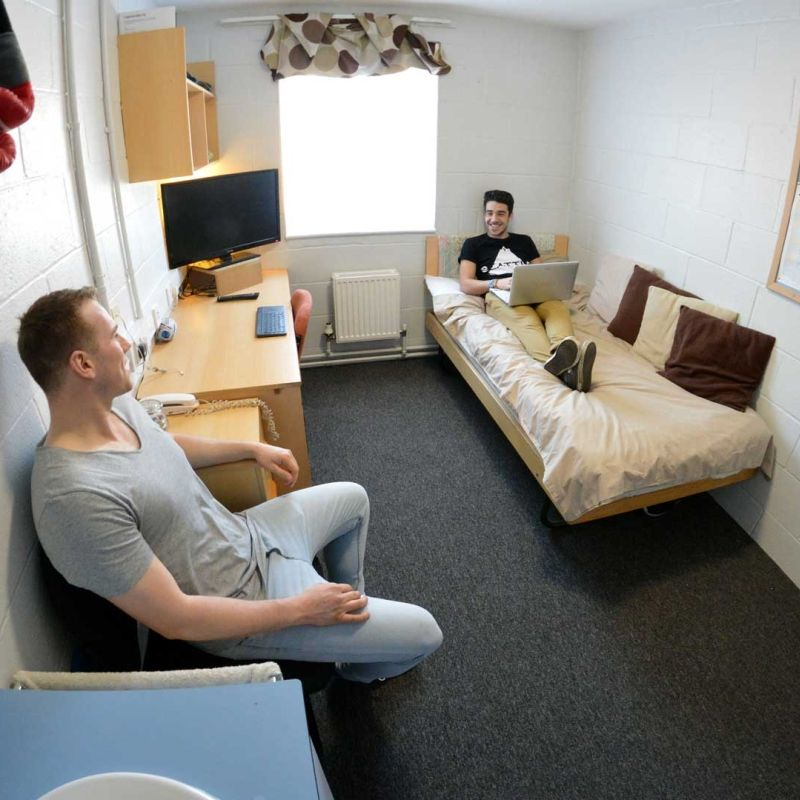 two students sitting and chatting in a standard room in Brook Street accommodation