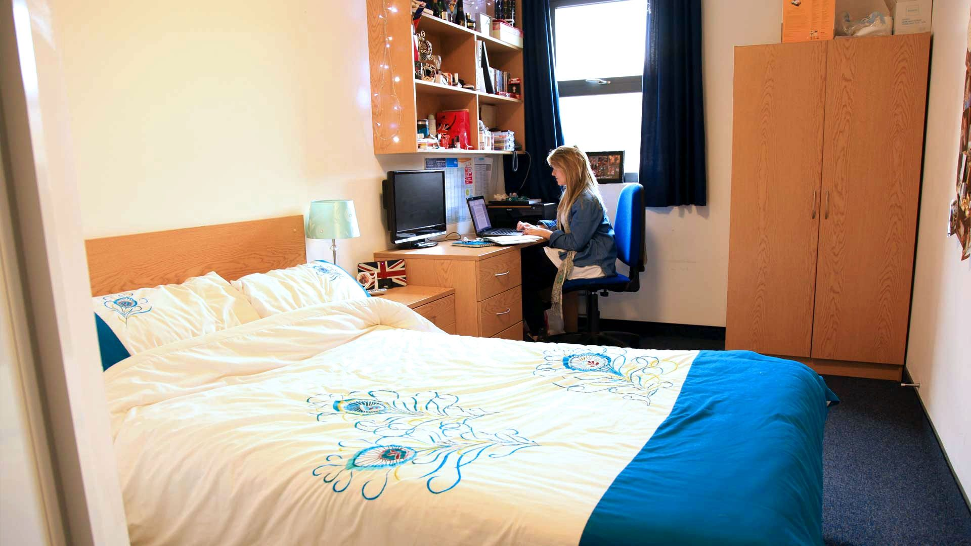A student sitting at their desk in a standard en suite